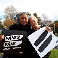 Two women standing together holding Fairs Fair signs